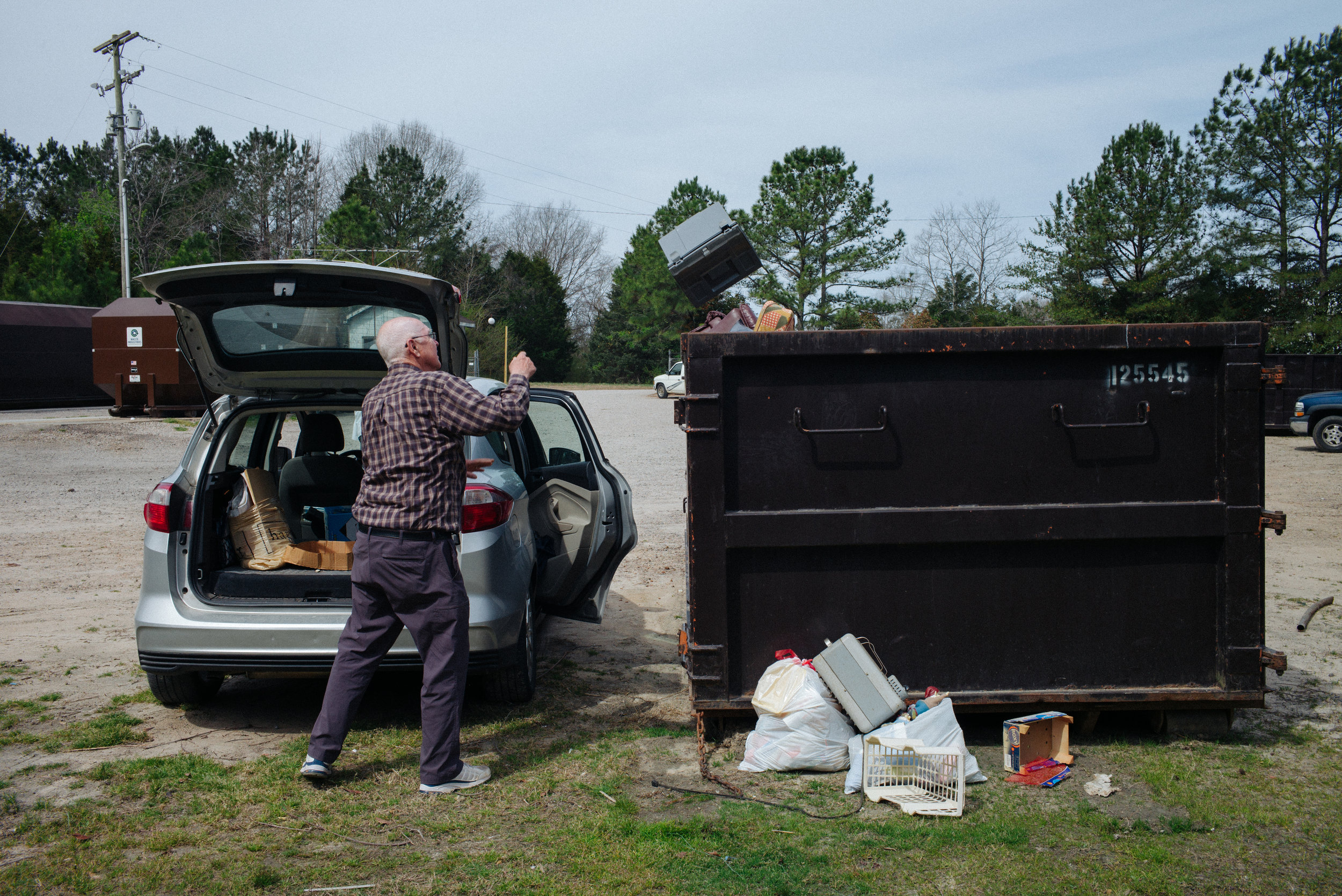 Thomas C. Field, 78, throws out trash on Saturday, March 25, 2017 in Littleton, North Carolina. The couple starts working cleaning their house and finding buyers on the market.