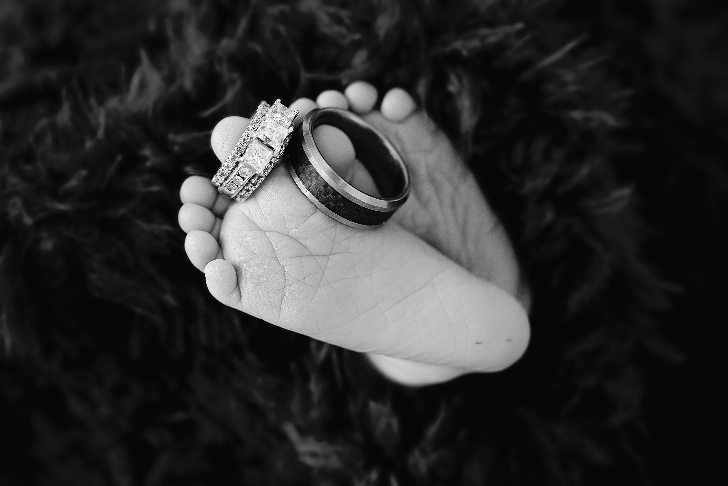 Baby toes holding wedding rings