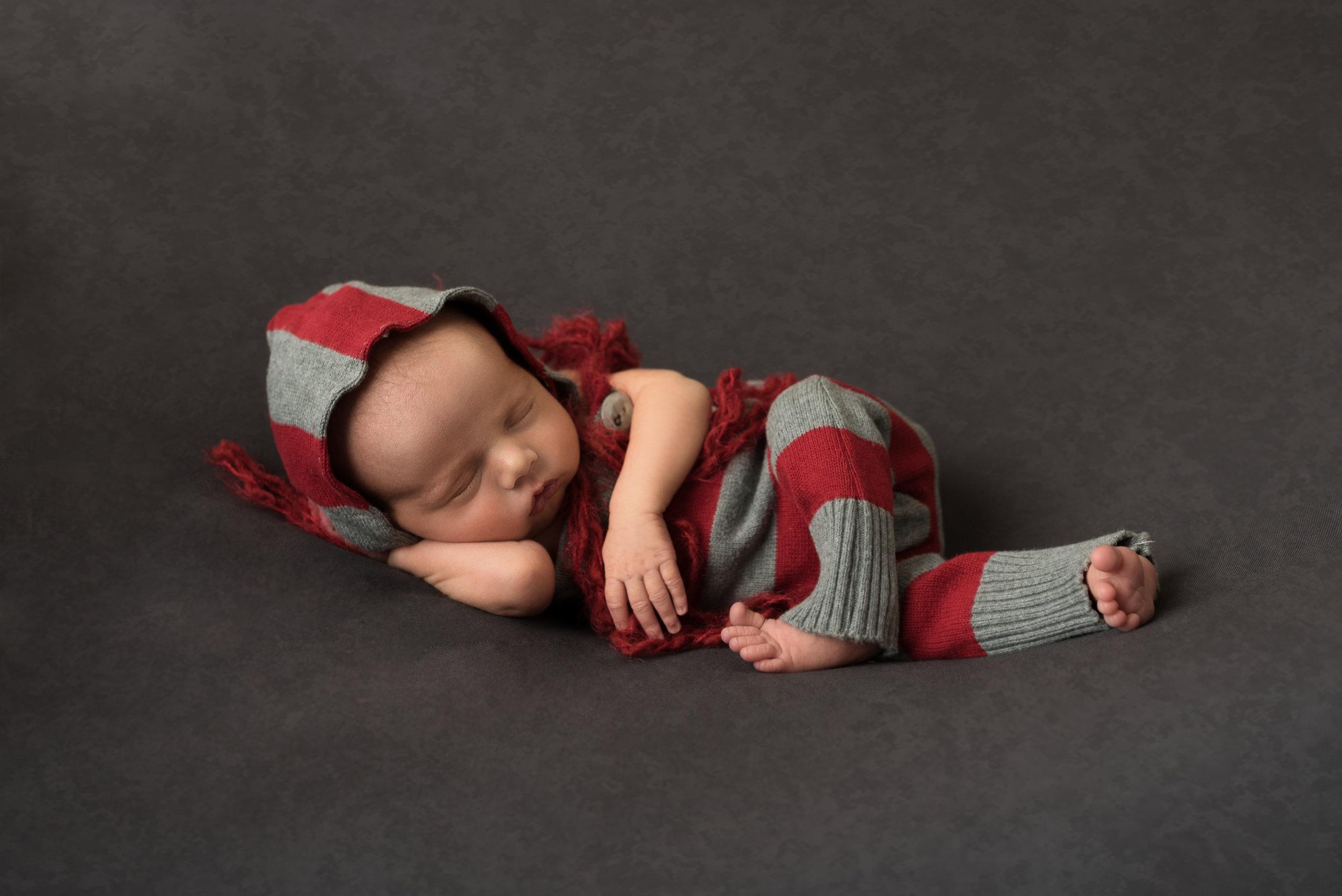 Baby boy is posing on grey
