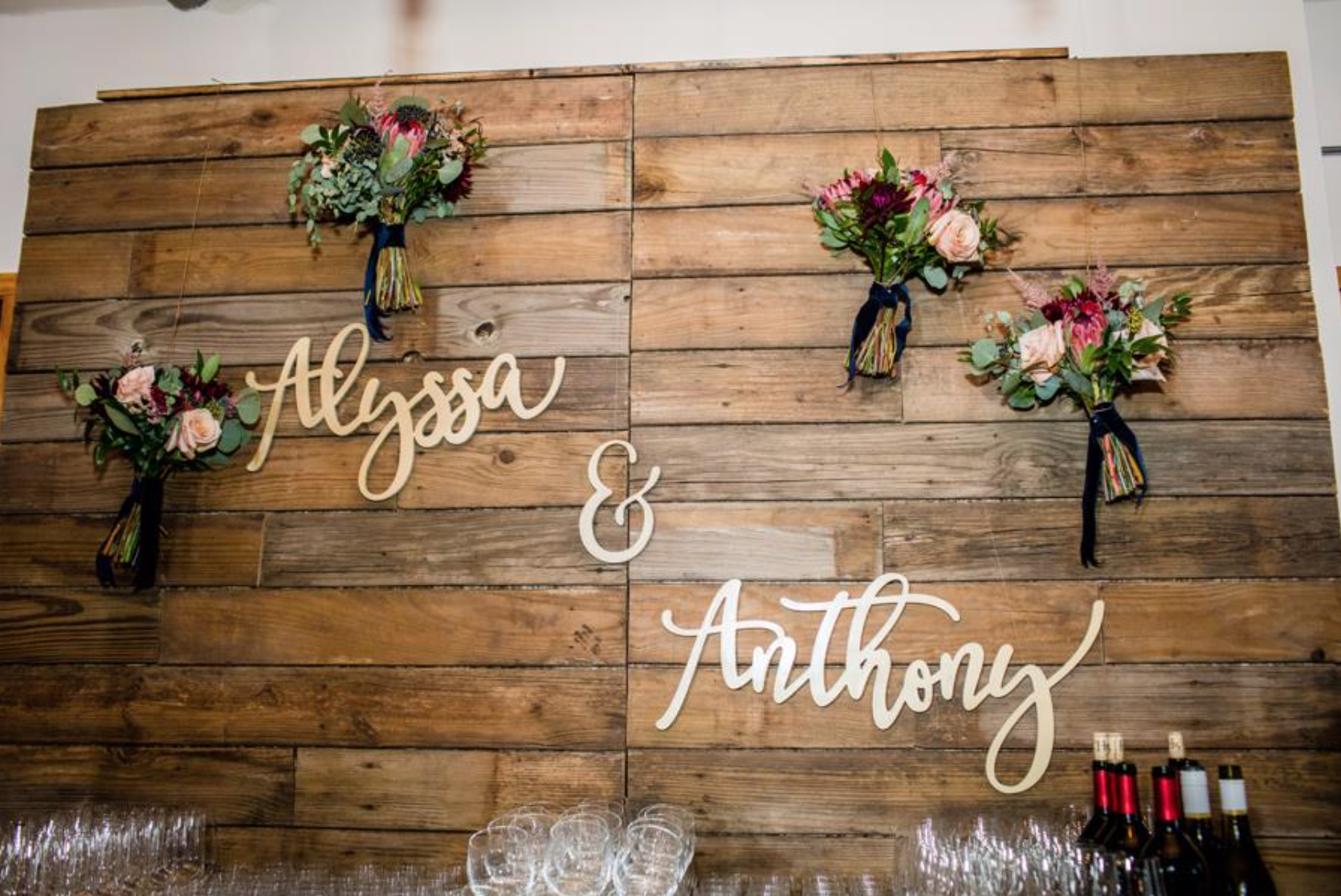 """We """"borrowed"""" the bridesmaids bouquets to add a pop of fall color behind the bar. They were of course given back at the end of the evening."""
