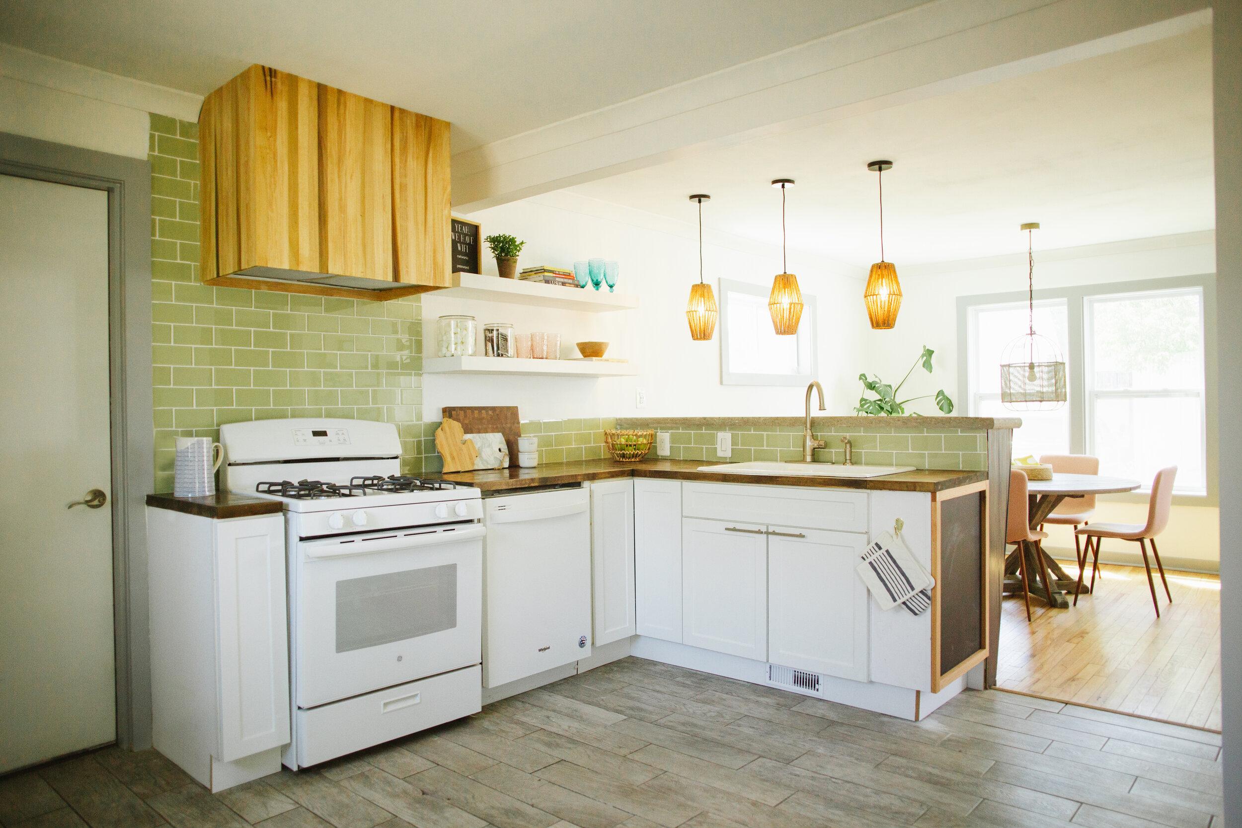 White appliances and a green glass backsplash add to the coastal vibe.