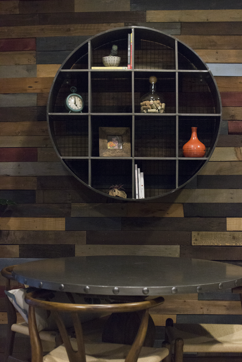 Pallet wall with round metal shelf