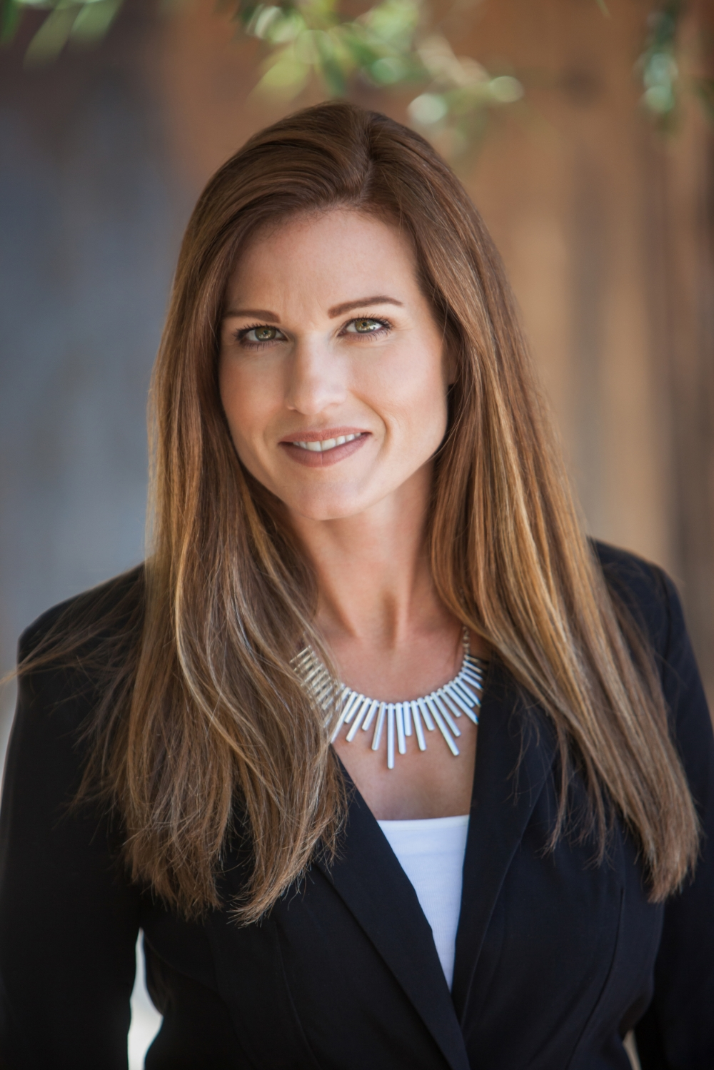 An outdoor, natural light professional Corporate headshot of a business woman in a dark suit. ©Photo by Val Westover Photography - Orange County California & Salt Lake City Utah. All Rights Reserved.