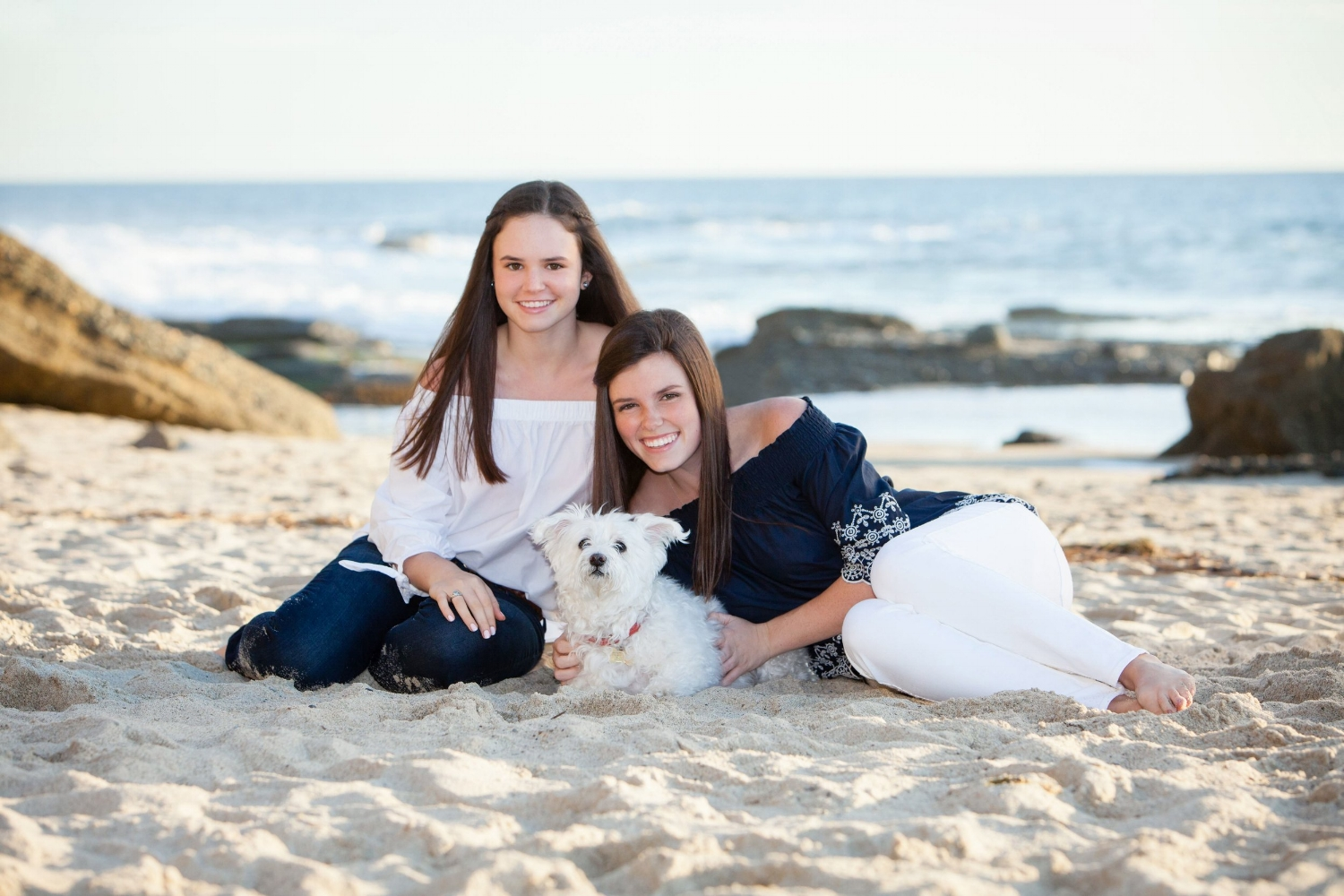Sisters cuddling with their dog at the beach.