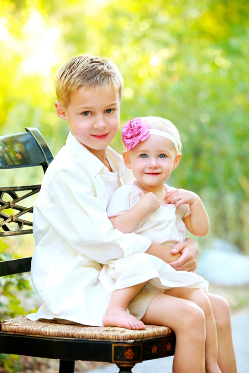 Beautiful young boy and girl outdoors in the flowers