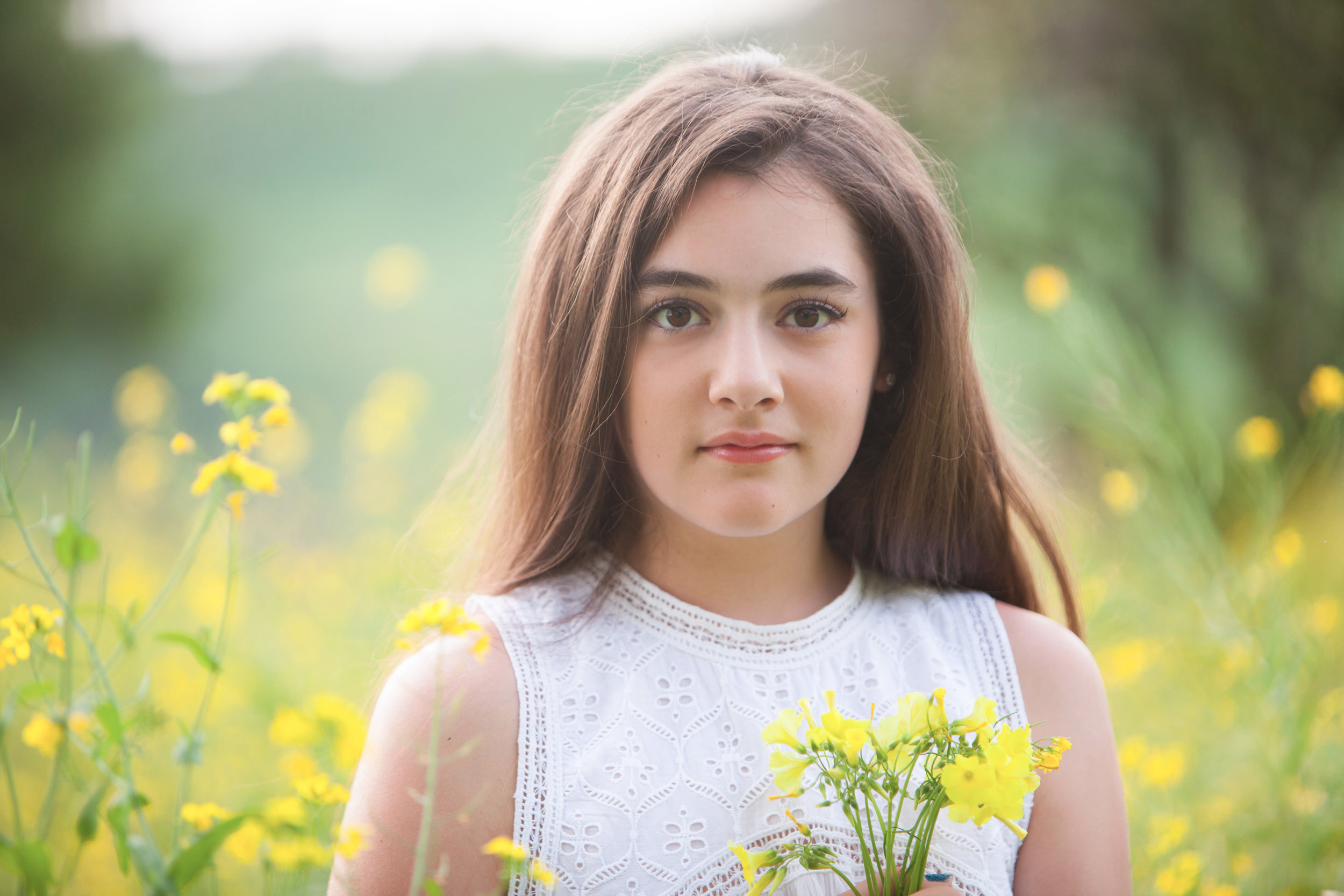 Pretty girl with long brown hair holding yellow flowers outdoors
