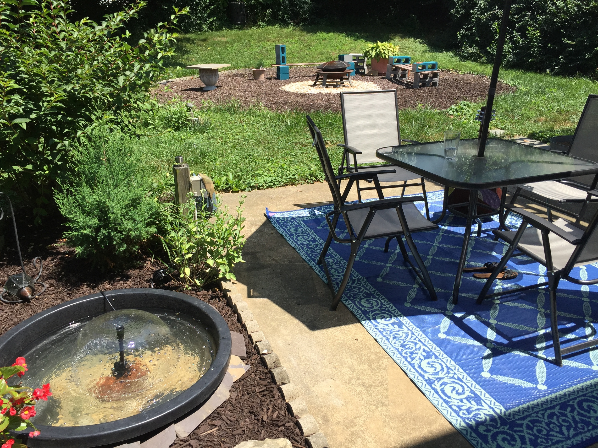 A view of my water fountain along with the patio and fire pit area I created in back.