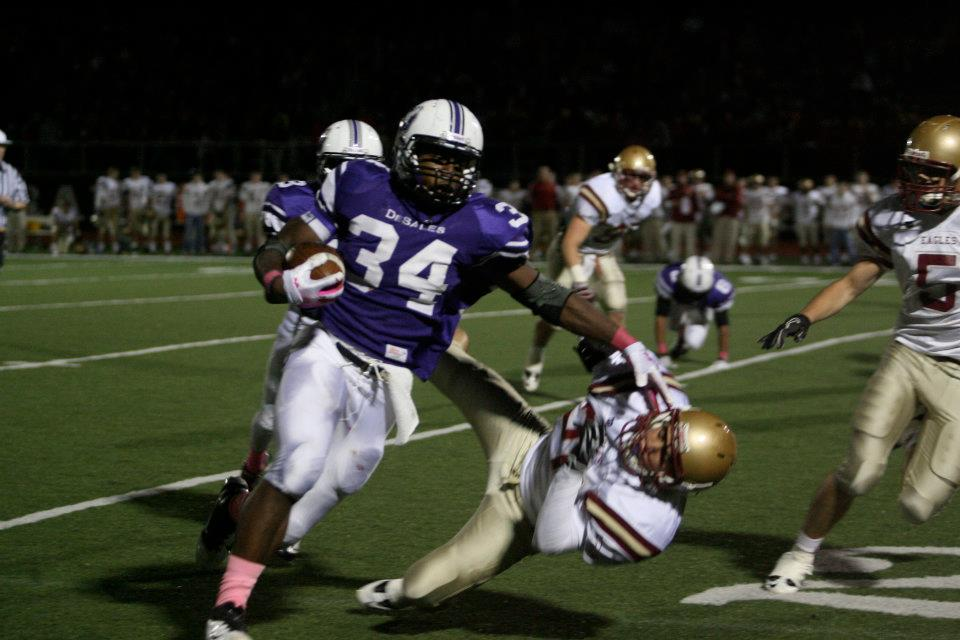 Warren Ball (34) delivers a punishing stiff arm, as part of his 195 rushing yards (photo credit - Barb Dougherty)