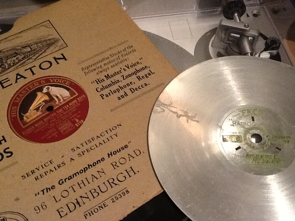 "The age-worn EKCO disc of 25/12/1937 next to my grandfather's copy of ""Eleven More Months and Ten Days More"" bought from James Beaton's Gramophone House."