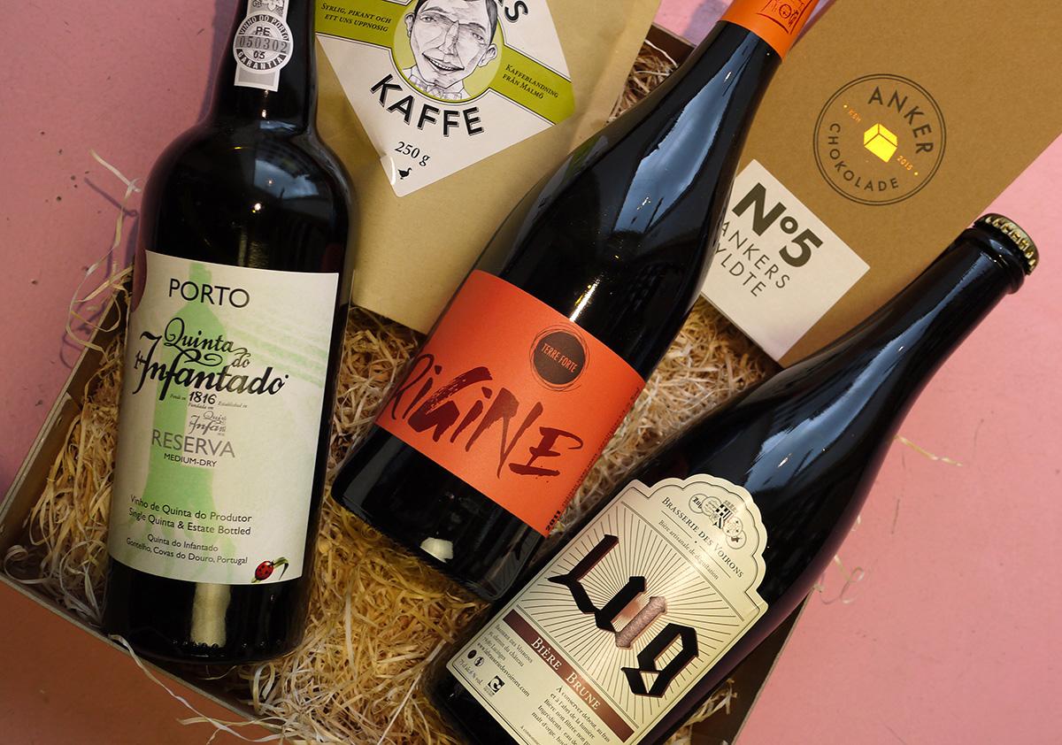 """I vores """"medium"""" gavepakke  kan indholdet variere mellem vin, spiritus, øl, portvin, cider, kaffe, chokolade, lakrids, nødder og andre delikatesser. Den afbildede pakke indholder, øko ruby portvin, øko Côtes du Rhône, mørk specialøl laver på økologiske råvarer, fyldte chokolader og specialkaffe. Den vil koste 560kr."""