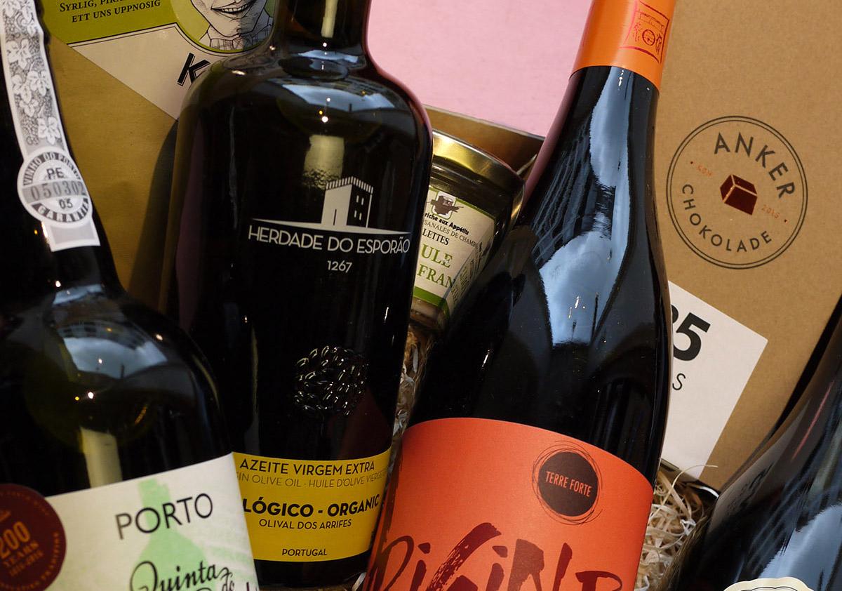 """Vores """"store"""" gavepakke  indeholder flere elementer end mediumkassen. Indholdet kan variere mellem vin, spiritus, øl, portvin, cider, kaffe, chokolade, lakrids, nødder og andre delikatesser. Den afbildede pakke indholder, øko ruby portvin, øko Côtes du Rhône, mørk specialøl lavet på økologiske råvarer, fyldte chokolader, specialkaffe, kyllingerillettes, mørk chokolade og ekstra jomfru olivenolie. Denne afbildede pakke vil koste 750kr."""