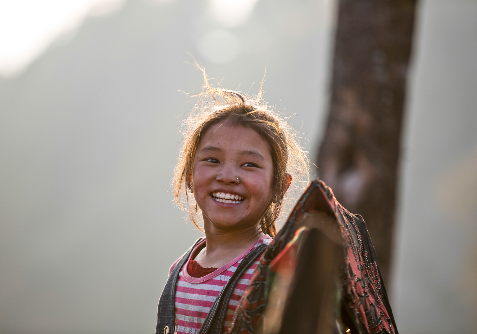 A girl in Nepal smiles past a UNICEF photographer in Barpak, Nepal in January 2016. 1400 homes were destroyed in her village in the 2015 earthquakes. Ethan and the New Zealand comms team were able to document and cover some of Nepal's recovery in 2015 ( © UNICEF/UN017159/Shrestha)