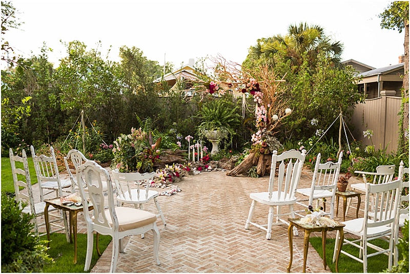 grace and serendipity, ashley victoria photograpy, fiore - the lacy oyster - one sided arch with crepe myrtle, reds, pinks, pearls and flowers - ceremony area with one sided arch, tapered candles, intimate and romantic setting, white ceremony vintage chairs from hemstitch vintage