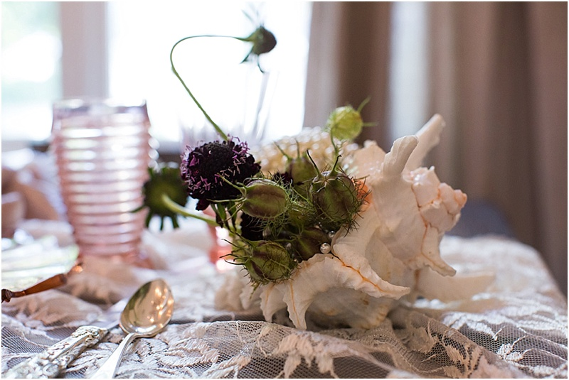 grace and serendipity, fiore, ashley victoria photography  - the lacy oyster - pensacola wedding styled shoot - intimate dinner setting with pink flowers, pearl pomander, roses, zinnias, dahlias, and lace tablecloth, and tapered candles