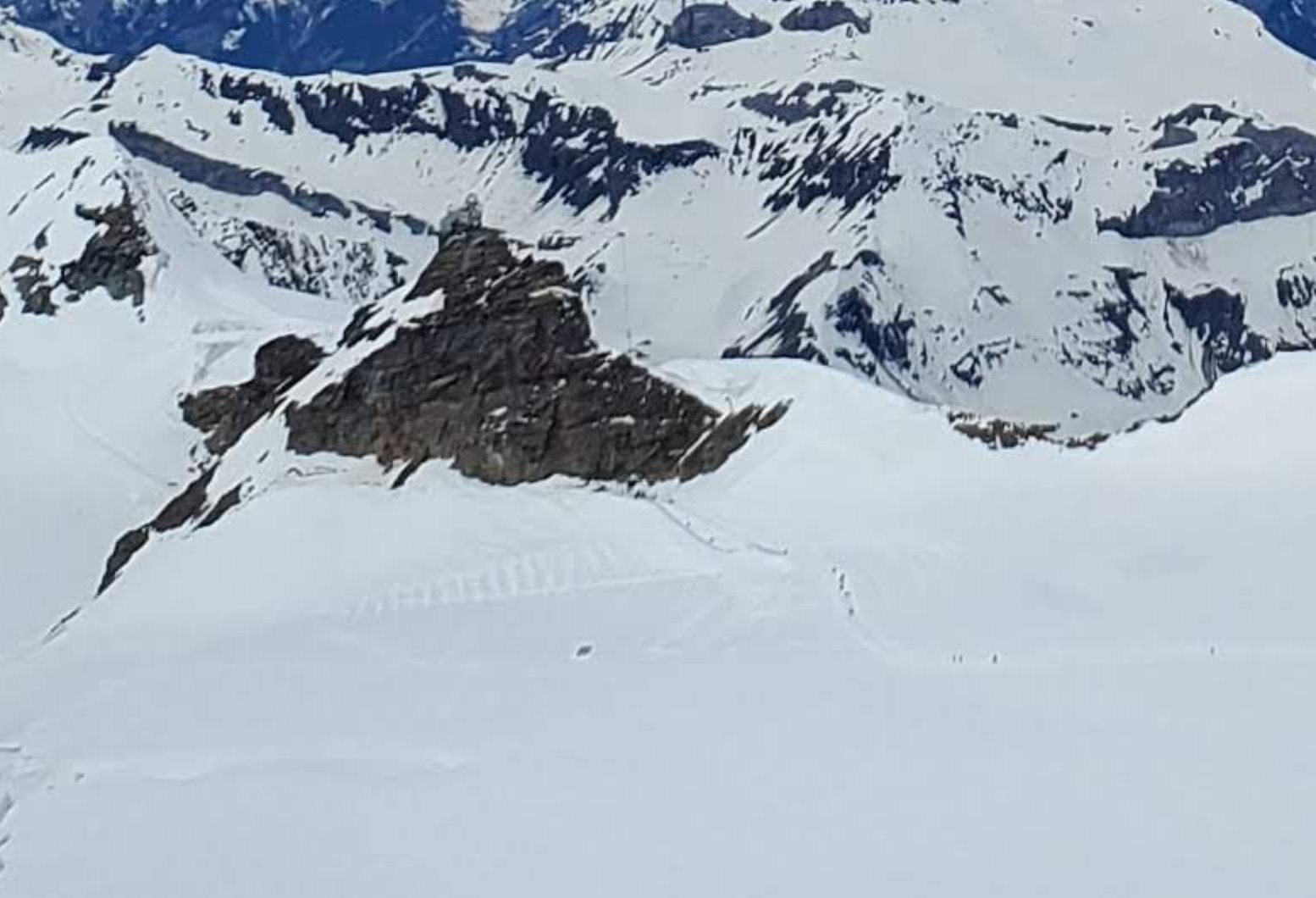 Zoomed in shot of the Jungfraujoch station (grey building atop the rocks). You can see the tiny dots of people walking on a groomed/safe path out onto the glacier.