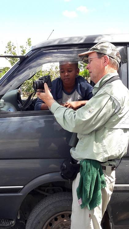 Shane on Barbuda showing a young local boy a photo of the warbler endemic to his island.