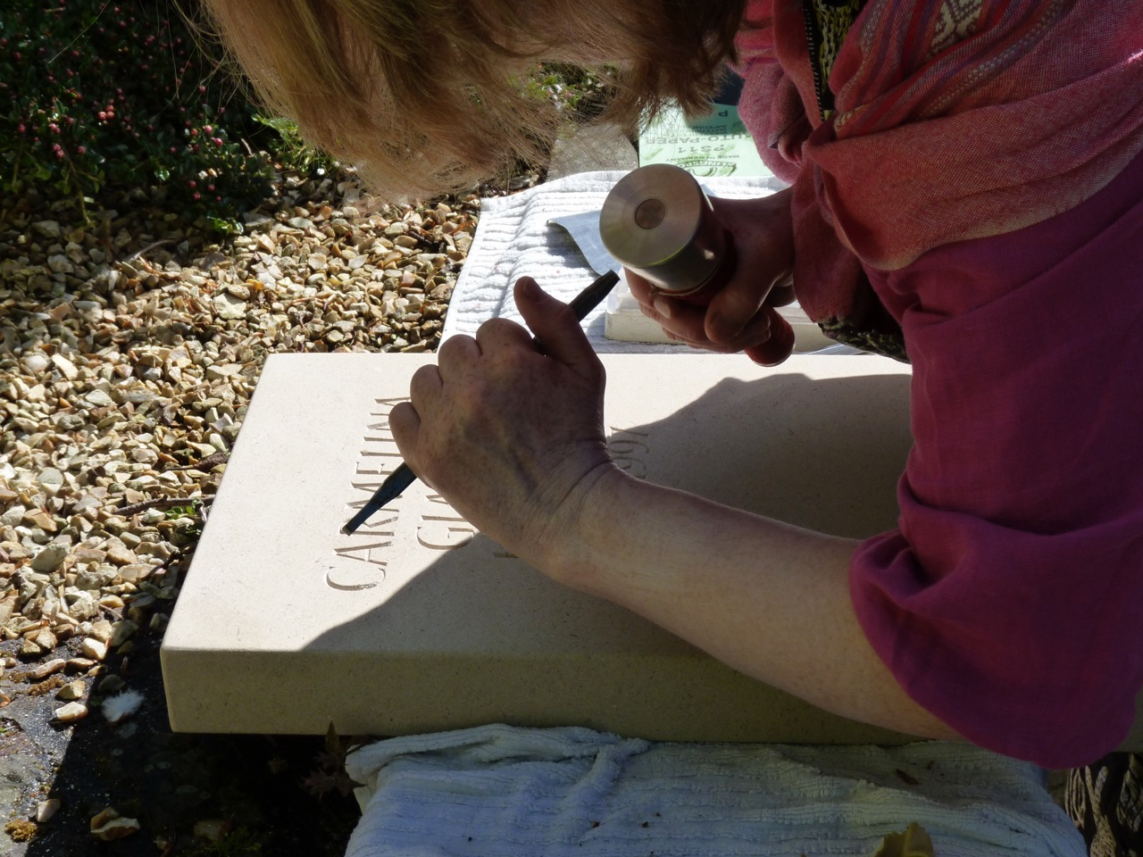 Working on a headstone, letters being carved in York stone.