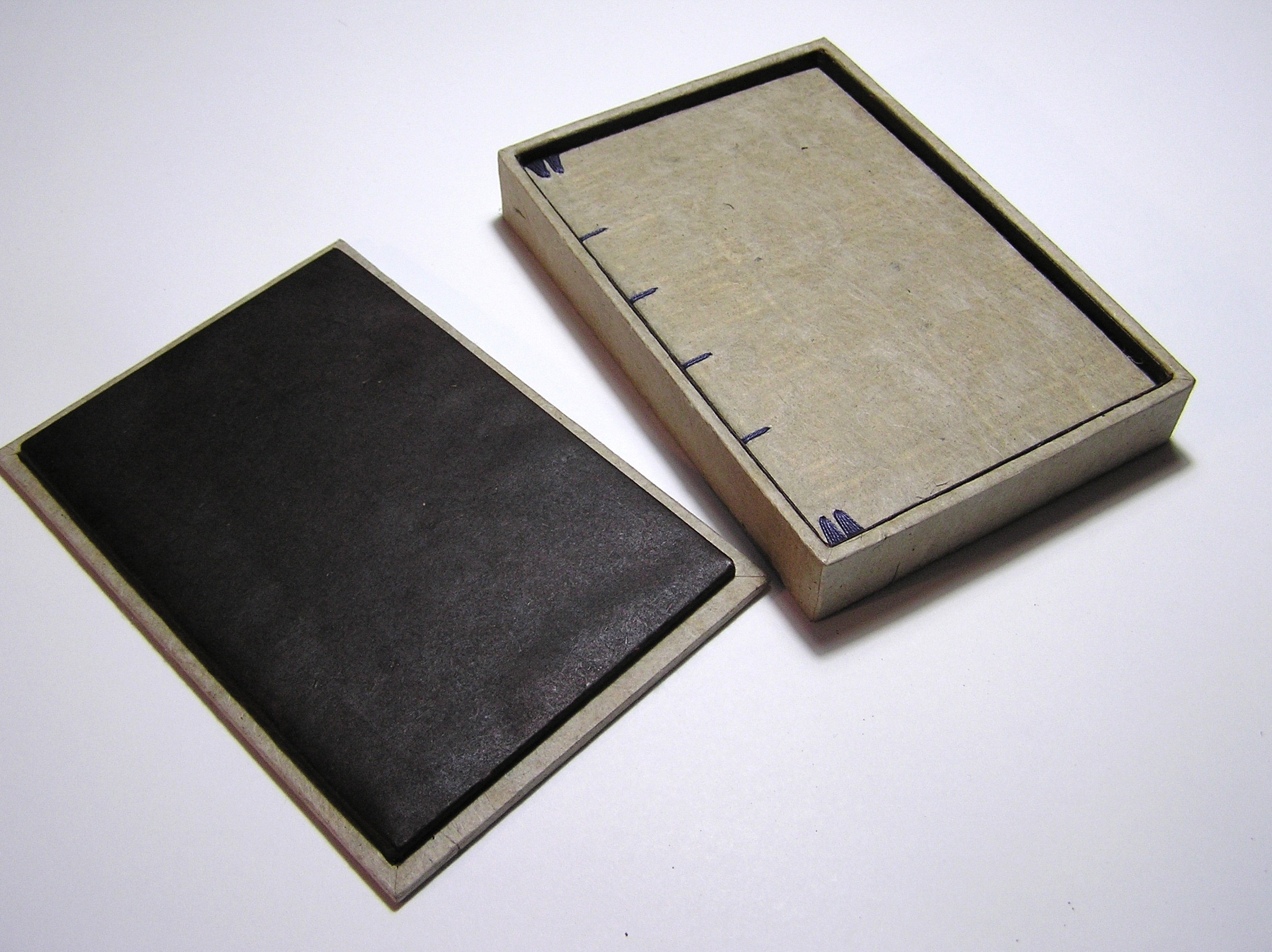 Small handmade book in a box. A poem is painted on the pages of the book as was commissioned for a wedding anniversary gift.