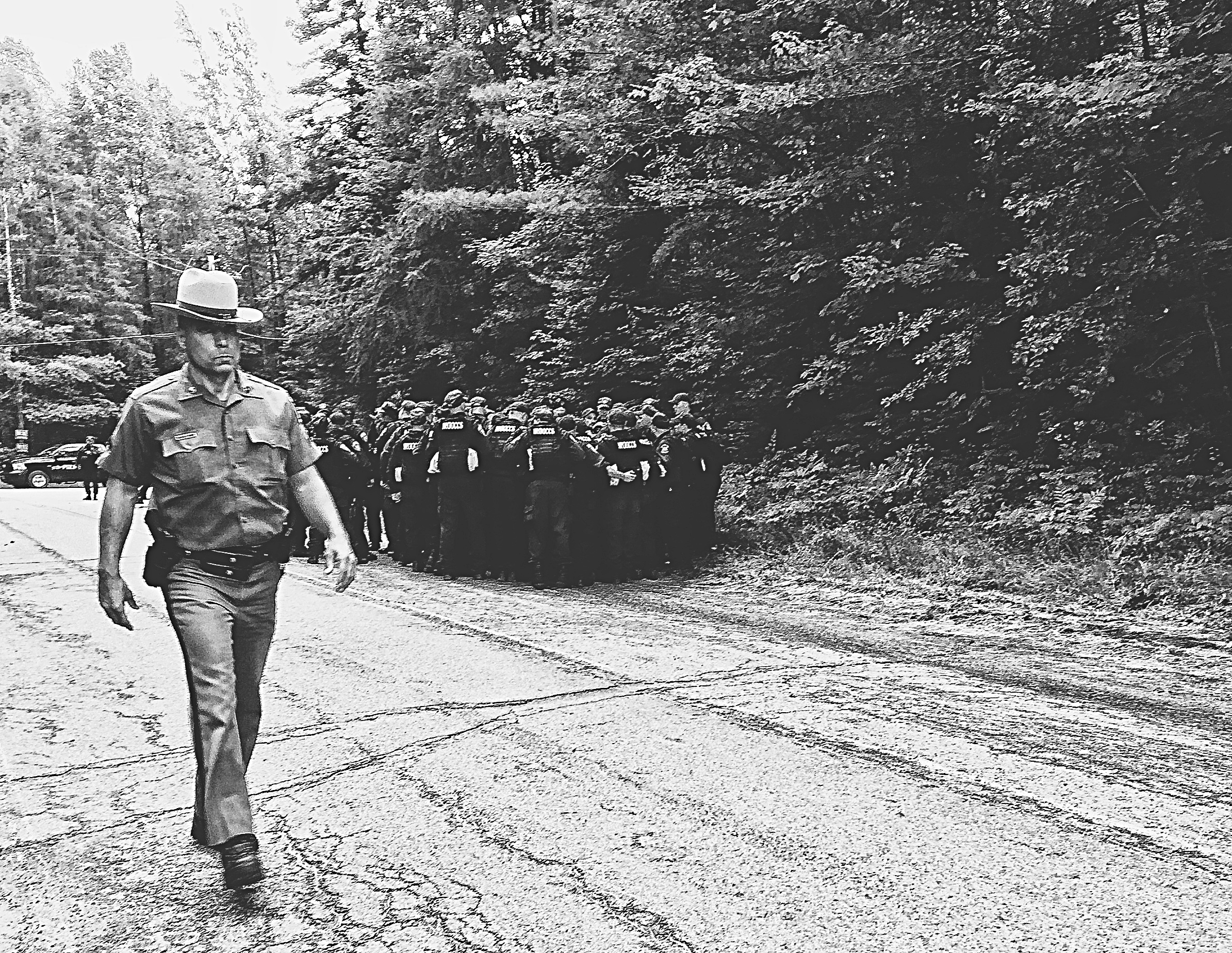 A New York State trooper walks by a group of corrections officers in Owls Head N.Y. The search for Richard Matt and David Sweat has moved to this area after DNA evidence is recovered from a nearby cabin. (Chelsia Rose Marcius/June 23, 2015)