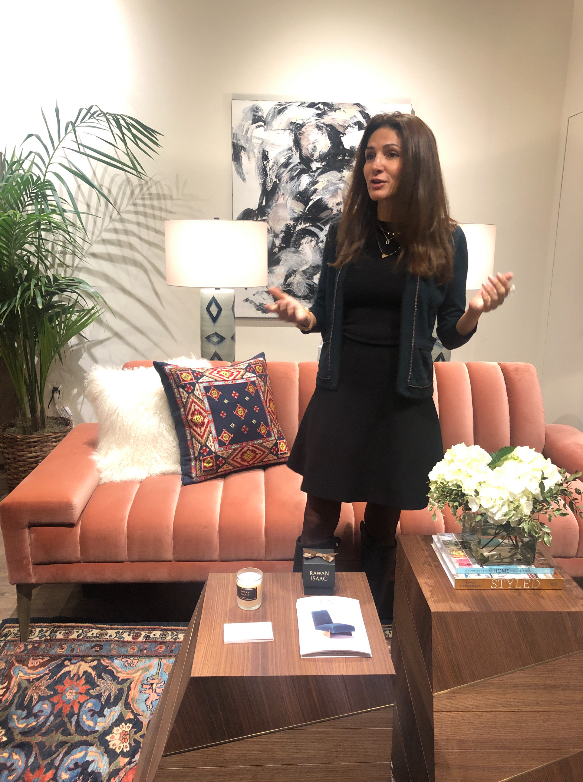 Designer Rawan Isaac between her sculptural side tables and the perfect pink tufted velvet sofa