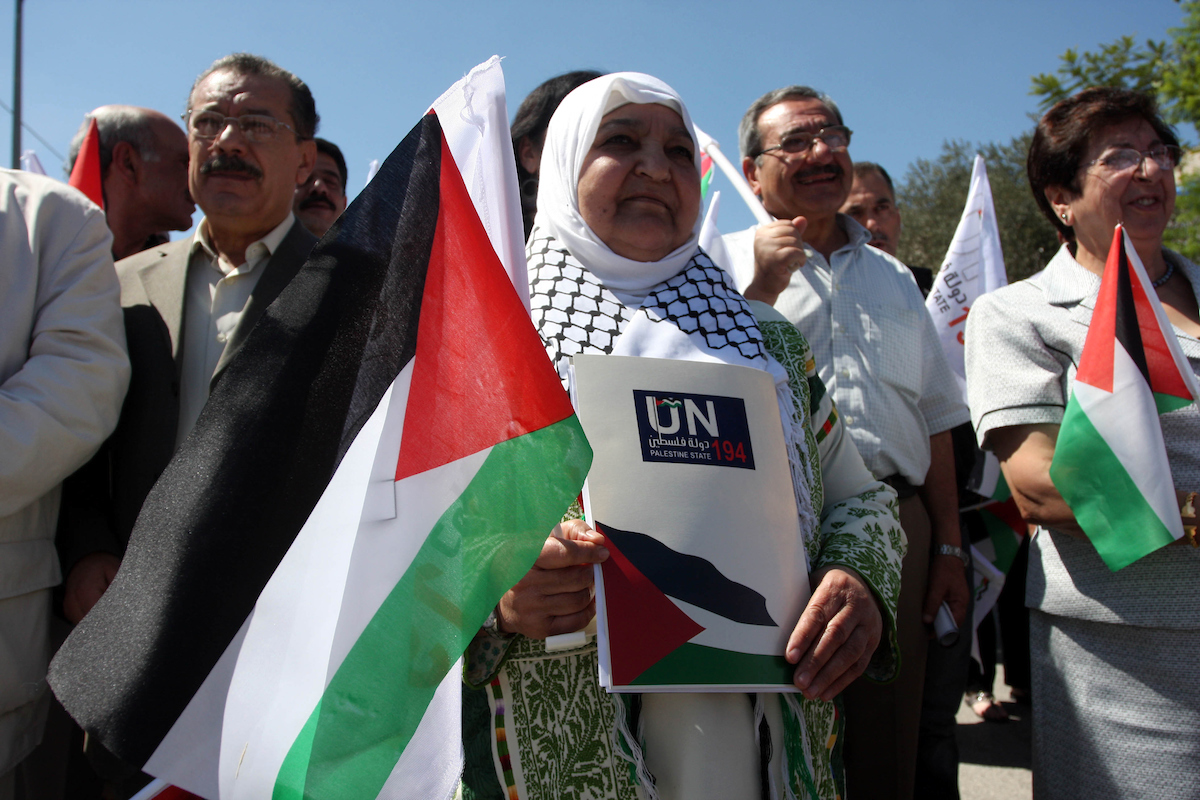 Palestinians hold banners and flags as they march during the launch of a campaign supporting a bid for Palestinian statehood recognition at the U.N, in the West Bank city of Ramallah on Sep. 8, 2011. A member of the campaign handed a letter intended for the U.N. secretary-general ahead of Palestinian President Mahmoud Abbas's bid to gain statehood recognition at the U.N. later this month. The banner reads: The people want Palestinian statehood membership at the U.N. (Photo: Issam Rimawi/ APA Images)