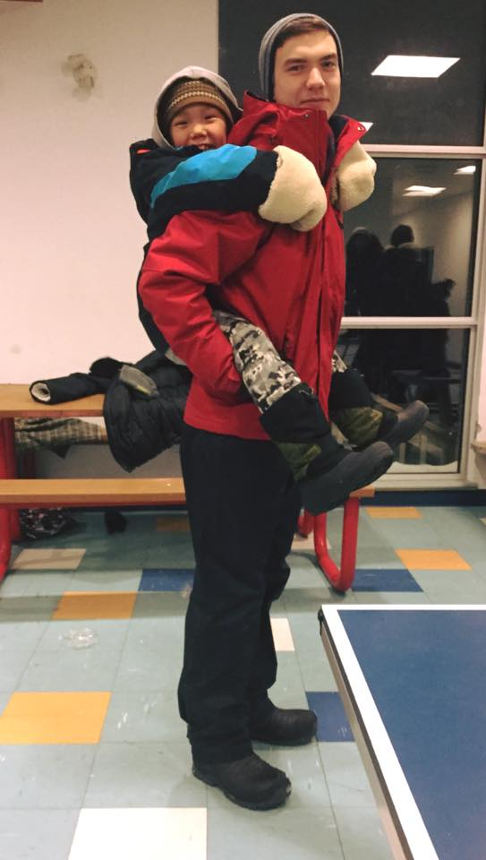 Patrick Hickey giving piggy back rides in Kangiqsujuaq.