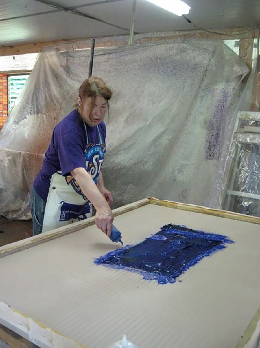 Kathleen is pulp painting on her large paper piece after a layer of abaca pulp was sprayed on the cloth to start.