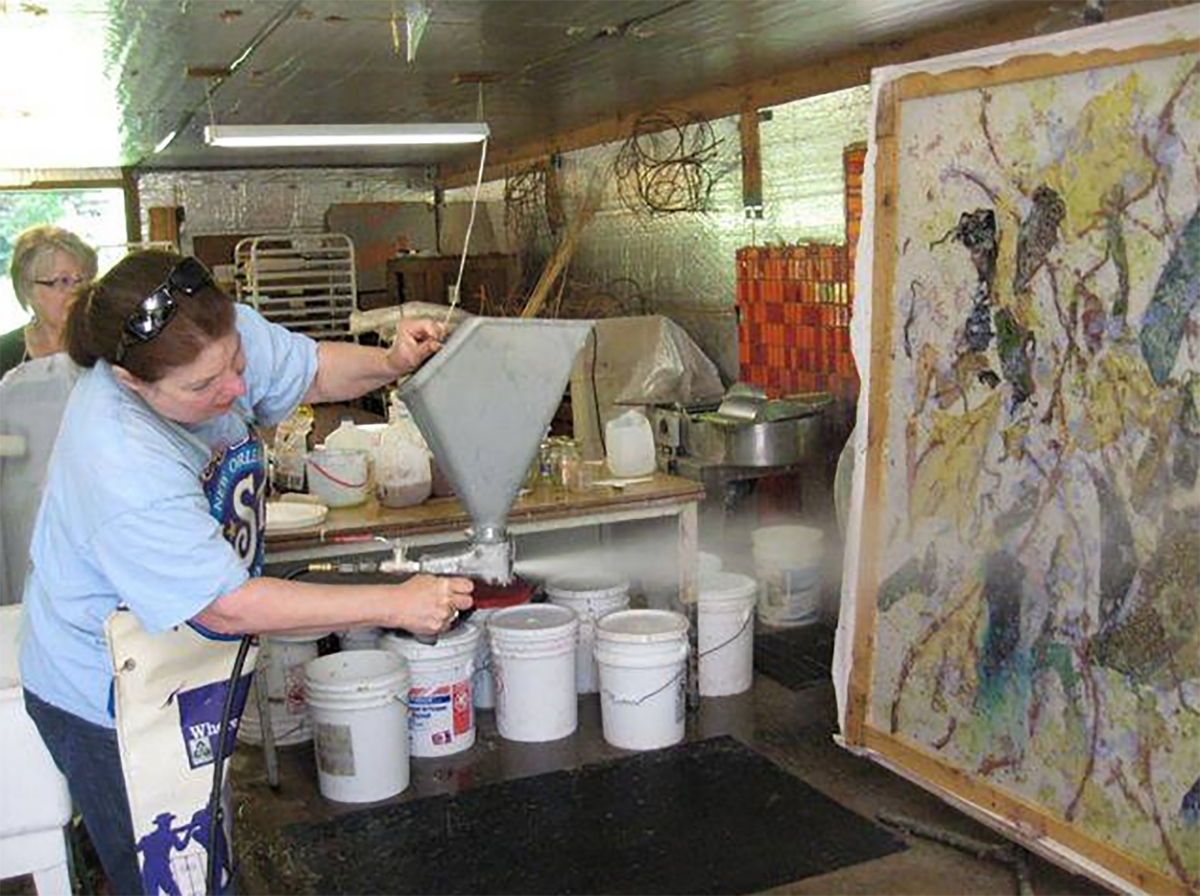 Kathleen is spraying another layer of pulp on her paper piece with fabric and plant inclusions between the layers.