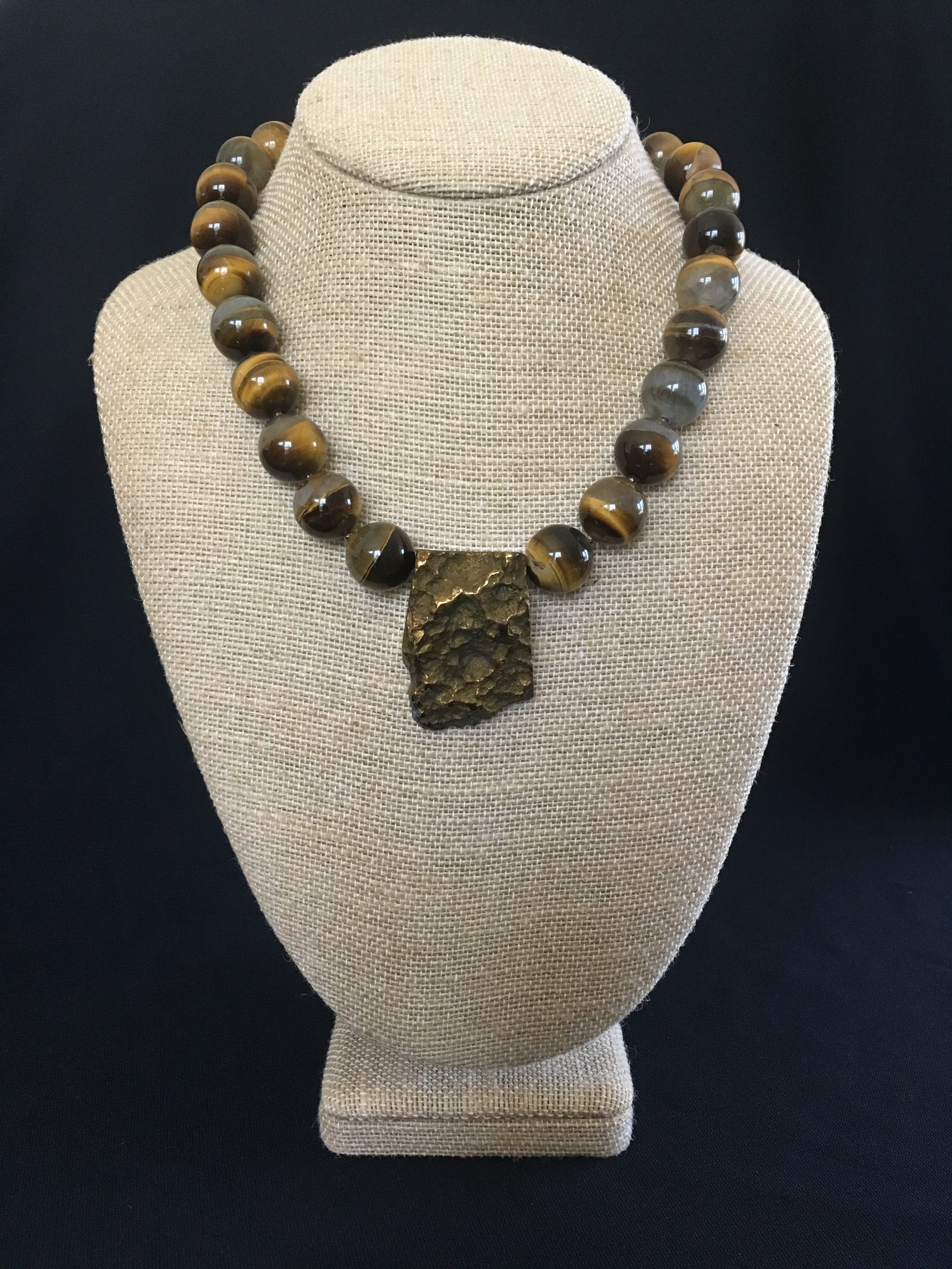 "Gold plated quartz center, tiger eye with sterling clasp. 18"" $125"