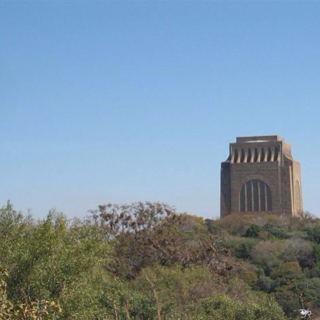 "Resonances of this disorientation visited me unexpectedly a few years later when, in August 2015, historian Roxanne Dunbar-Ortiz described the creepy place, as she said, that is the Voortrekker Monument in Pretoria, South Africa. In attempting to explain how she felt about approaching this structure, witnessing it, she talked around a feeling that I thought, even in her lack of distinctly articulating it, I could very clearly understand and relate to.  She was telling me that day about visiting the Voortrekker Monument and how, following the release of Nelson Mandela after 27 years in prison, and the end of apartheid in South Africa, the African National Congress left intact many of the monuments and museums which glorified apartheid, but inverted their narratives in one way or another, displaying in certain cases more accurate accounts of the historical record. Inside the Voortrekker Monument, she explained, one finds representations of the colonizing of South Africa which look uncannily like those representations of the colonizing of the U.S. It may as well have been the same artists, she told me, as had painted many of the famous images of the settling of the American West, complete with calistoga wagons; only, of course, in this case there were no Lakota or Apache clashing with the voortrekkers. Instead there were the Zulu.  But in talking about the sense that she had, not only from that uncanny analogue, but also from the structure itself, the feeling with which she was struck and indeed which had left her struck, Roxanne seemed less able to find the right words than when describing almost anything else that day. I remember, particularly, that she used the word ""place"" repeatedly, saying ""that place"" many times in one breath. She impressed on me that photographs do no justice to the immensity of the monument. I felt I could entirely imagine the unsettled awe that the place had inspired in her, and wondered if we had not actually had analogous experiences in approaching such massive, unlikely structures, whether intentional or incidental.  Later that day, I met a friend for dinner and he asked me if I had heard that Mount McKinley had been renamed Denali."