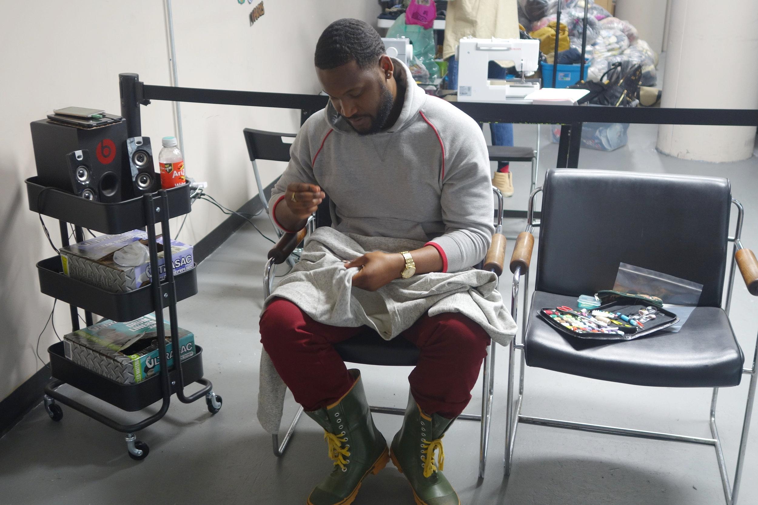 Jonathan Mckinnon, Founder (Men Of Thrift) hand-sewing a patch.