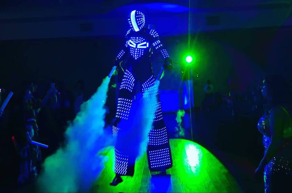 TI BOT - Hire our impressive 8 to 10 foot led robots for your event. A grand visual experience to impress your guests with one the newest entertainment ideas around.It's sure to boost the party atmosphere at your event, surprise the guests and have them super excited about interacting, dancing or taking snaps with a TI Bot.A great entertainment choice for corporate events, weddings, milestone birthdays and more.