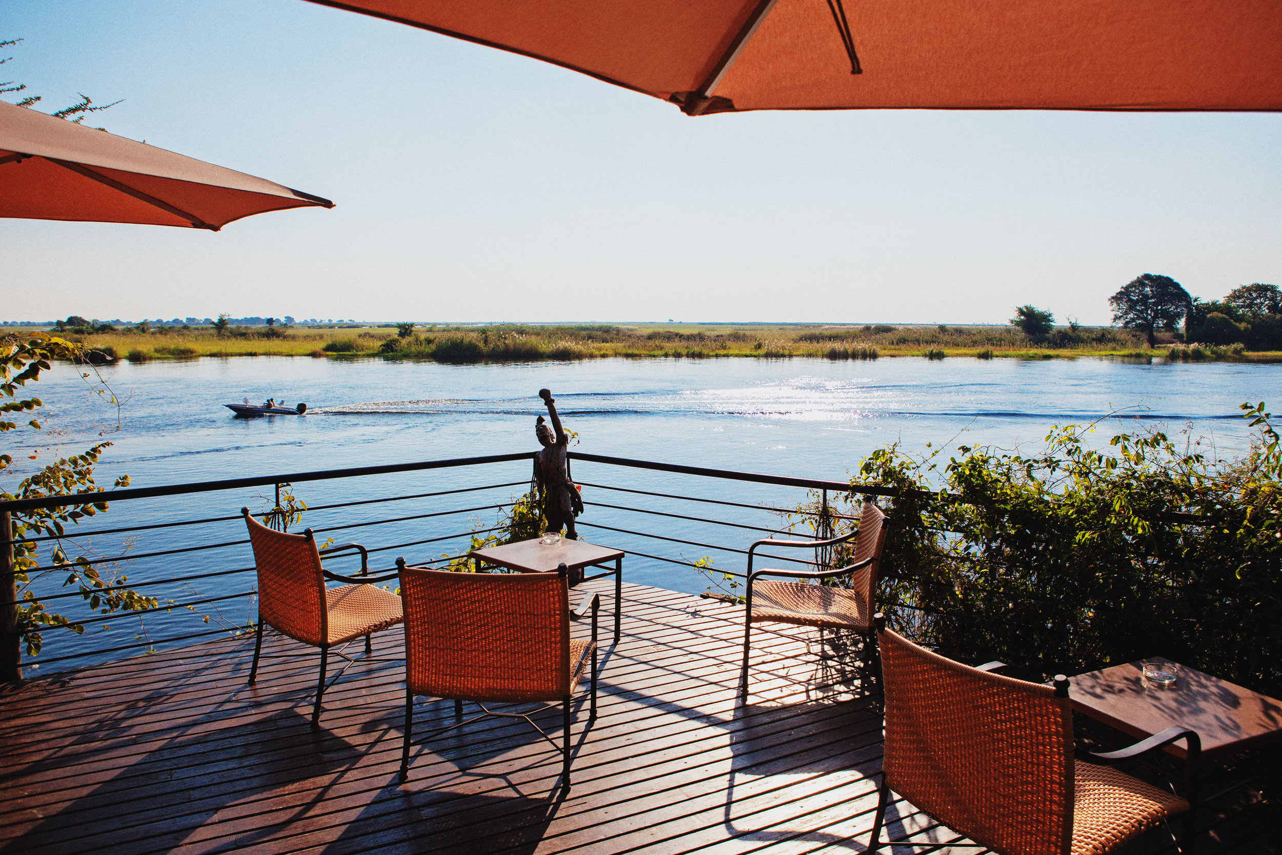 NATURAL BORDER  ::  The patio furniture sits firmly in Botswana, while the opposite grassy riverbank grows in Namibia.