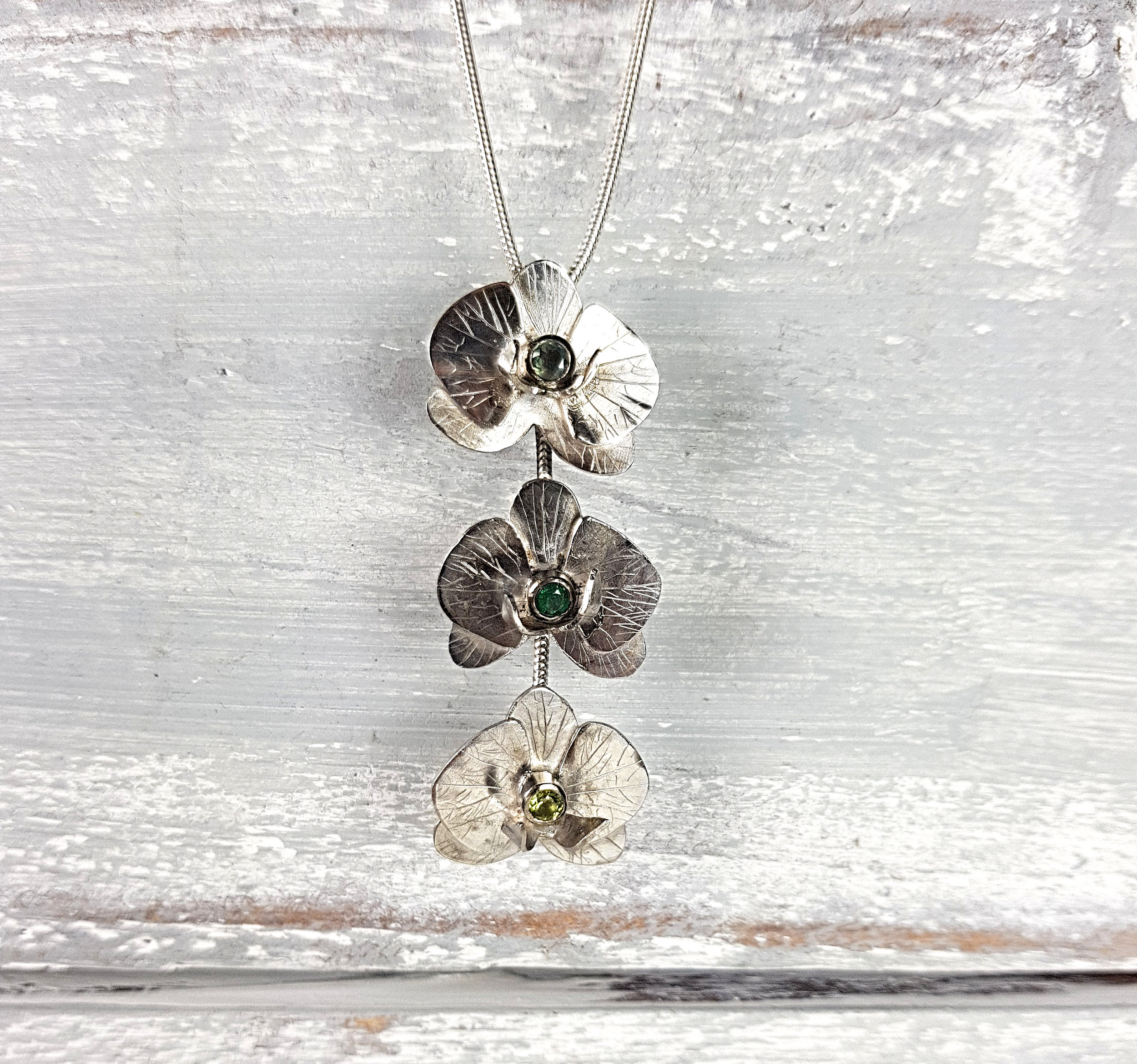 Jason commission a necklace for his sister. She loves orchid flowers so this was a little out of the norm for Shannon.  Set are the three birth stones of Jason's nieces. Alexandrite for June. Emerald for May. Peridot for August.