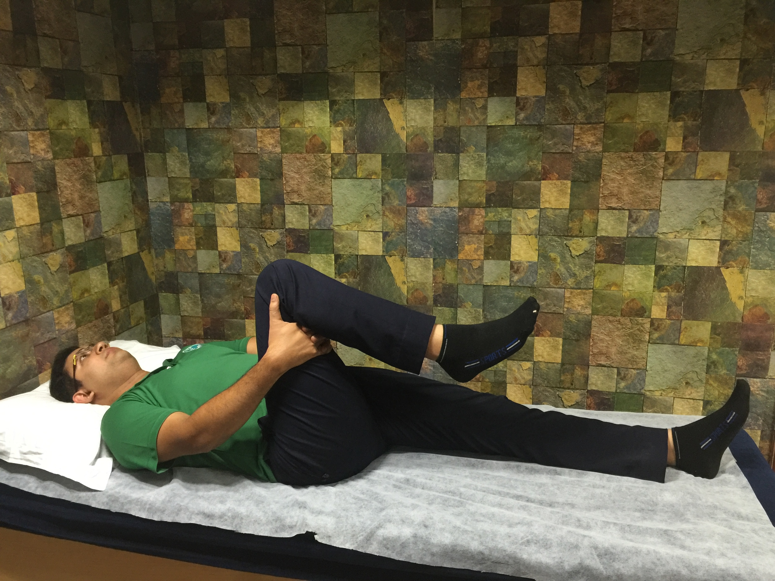 Lie down on your back with both arms flat on the floor. Bend both knees. Grab your right left behind the knee with both hands.