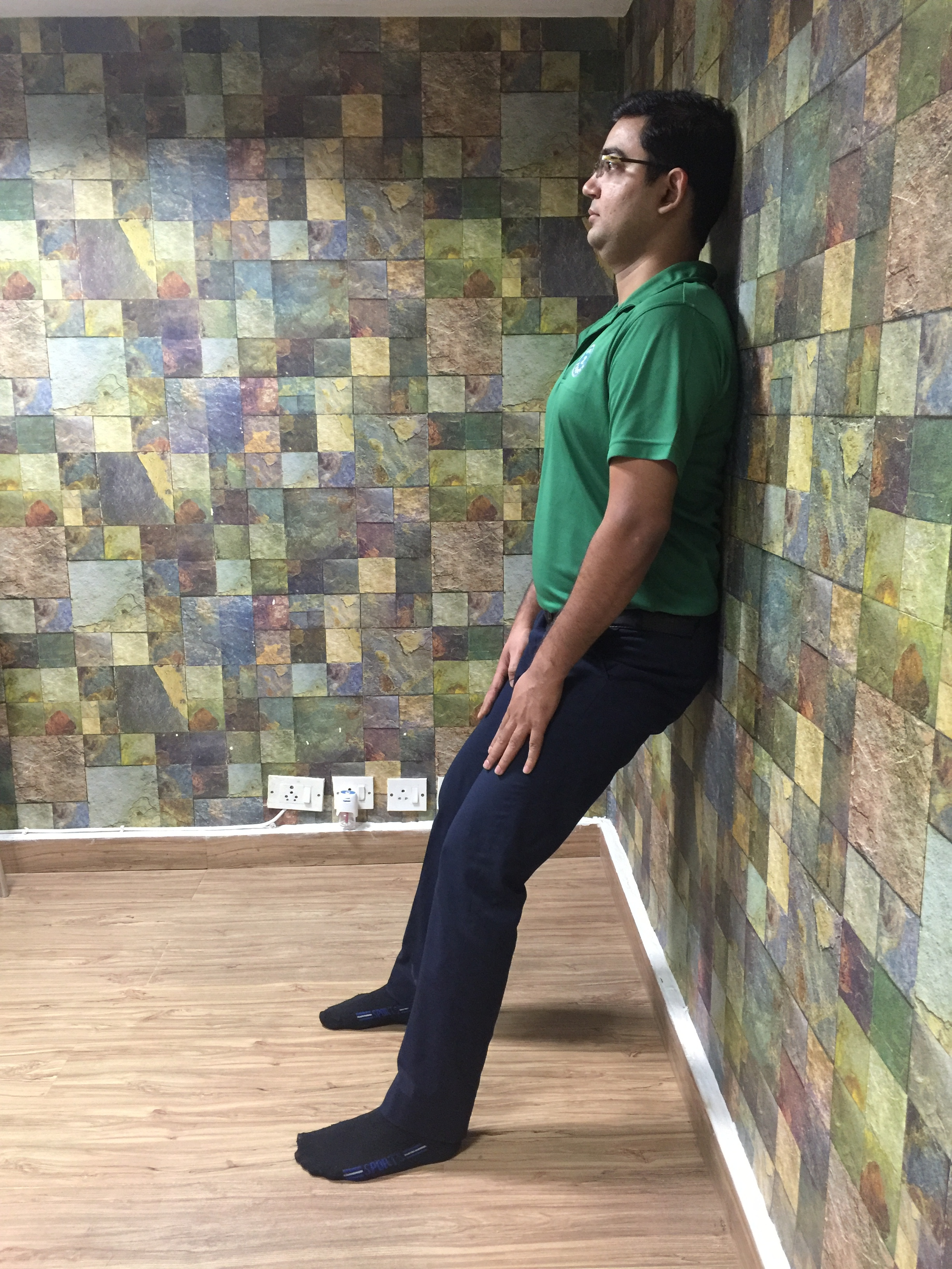 Lean with your back against a wall. Keep your feet shoulder-width apart and about 2ft from the wall.