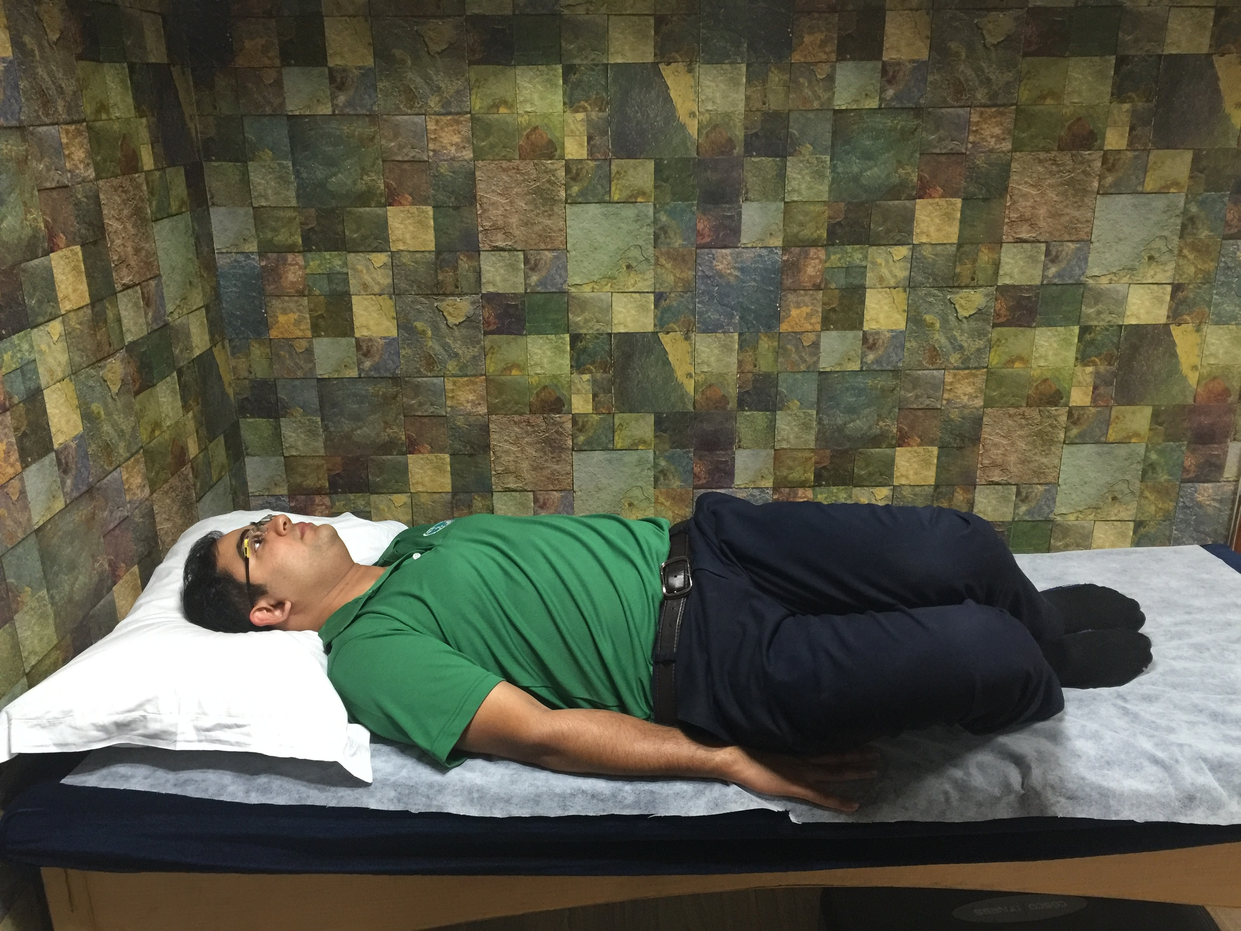 Slowly roll your knees first to the right; keep your upper trunk still; your left buttock should only very slightly come off the bed/mat.