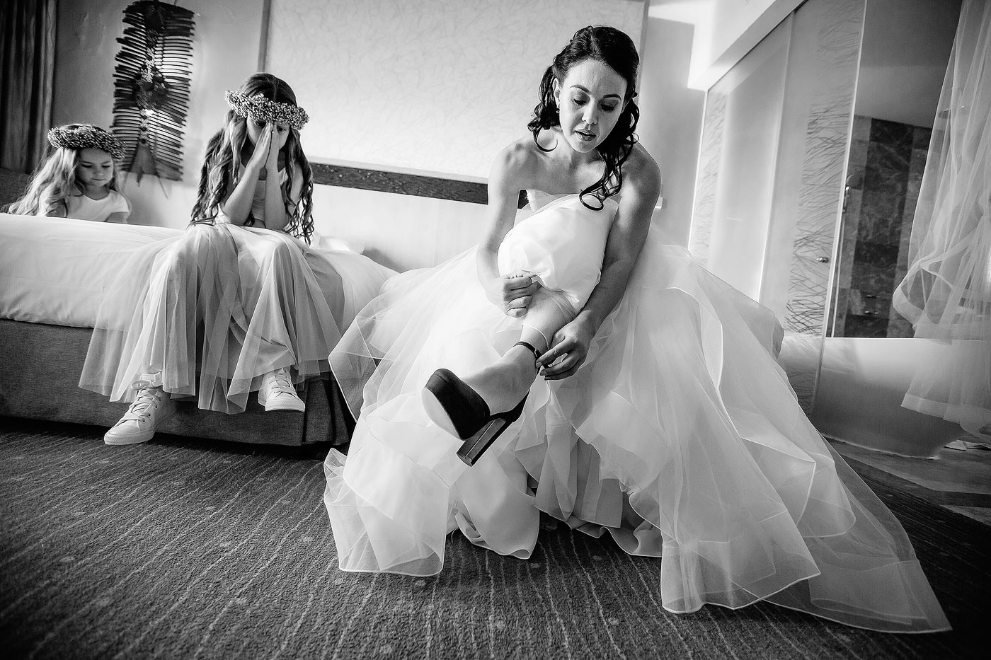 Bride putting on shoes in Bridal Room with Flower Girls