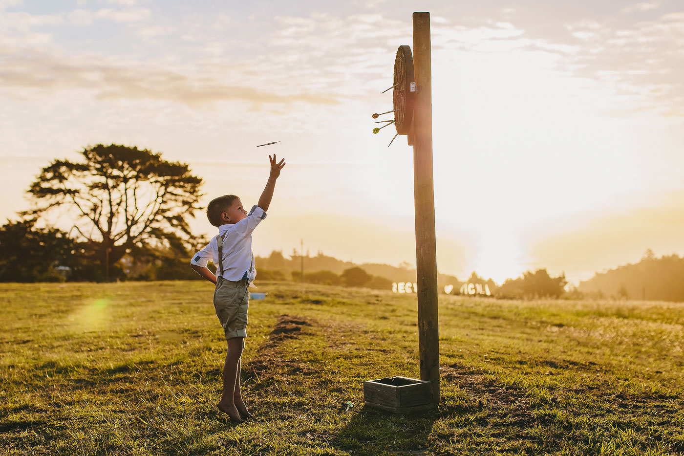Ringbearer at a wedding in South Africa playing Darts at Sunset.