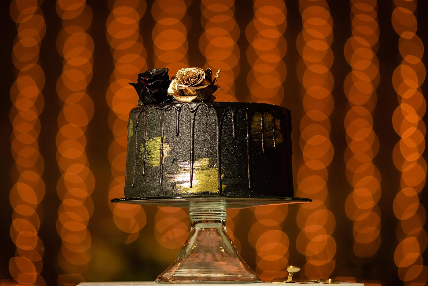 Black and gold wedding cake with gold details and fairy lights.