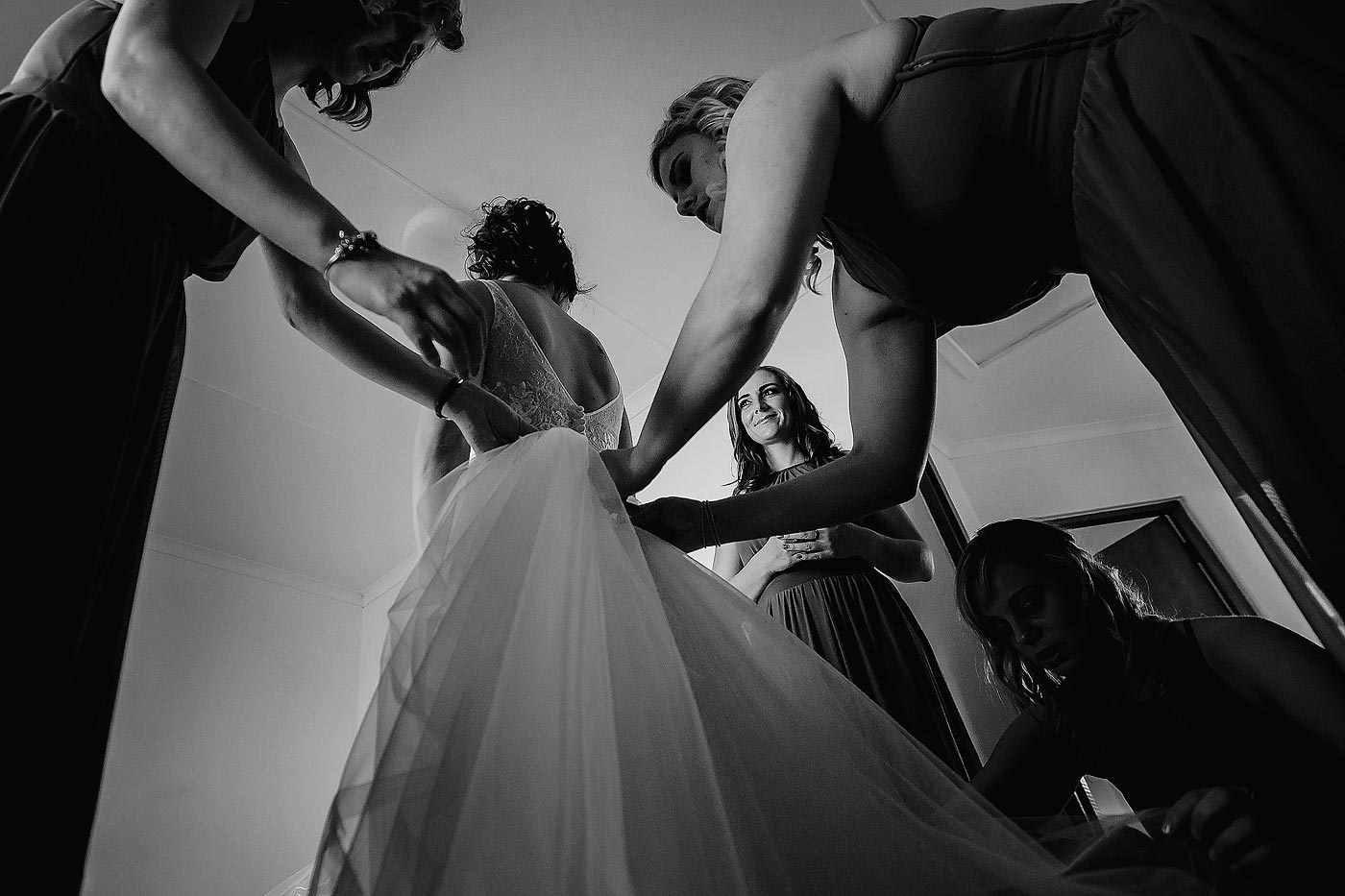 Copy of Bride getting into wedding gown before the wedding ceremony with bridesmaids