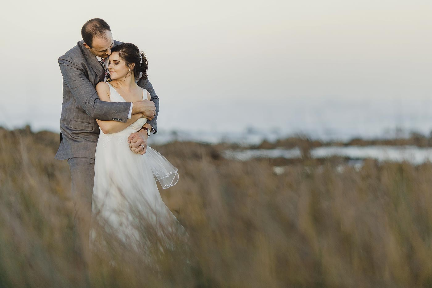 Copy of Classic Wedding Photo Pose in reeds at the ocean.