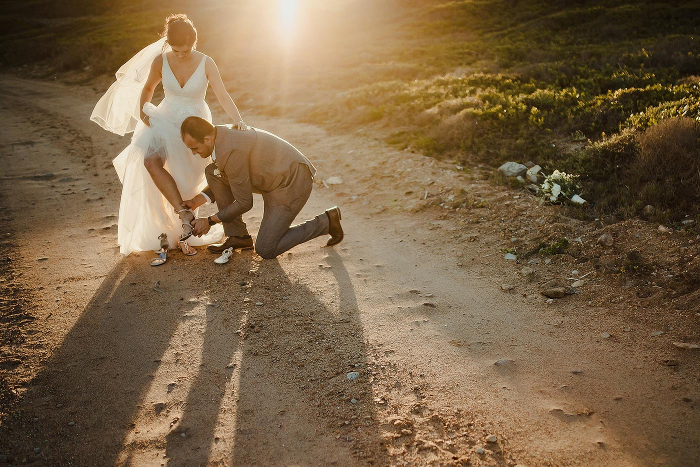 Copy of Wedding Couple at sunset with groom helping bride with shoes.