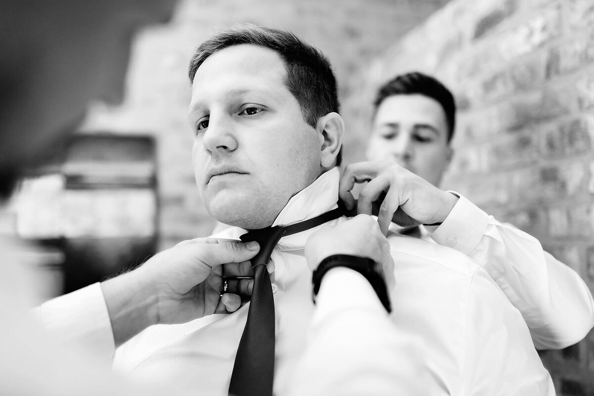 Groomsmen are helping the groom putting on his tie before the wedding ceremony in Waboomskraal, South Africa.