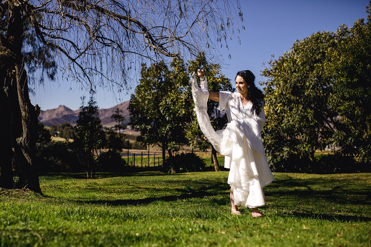 A bride holding her wedding dress in a Garden near a venue in Waboomskraal, South Africa.