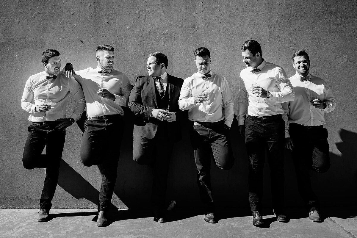 Groomsmen dressed in Groomsmen style stading with drinks againts a wall in the Waboomskraal Valley of South Africa.
