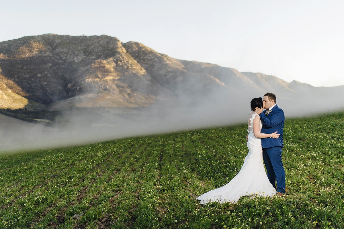 A big wedding portrait in a farm landscape with smoke in the backround.