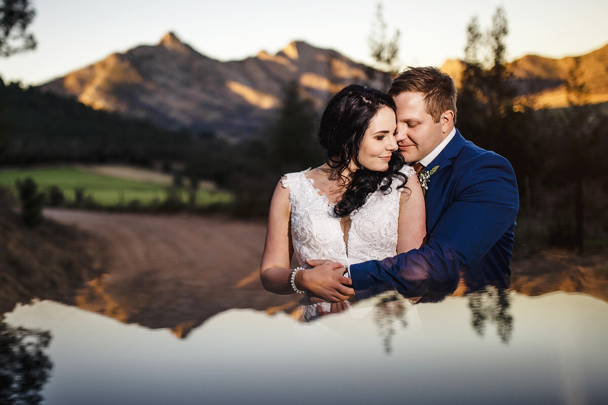 A creative wedding portrait with moun tains in the backdrop at Sunset in the Garden Route.