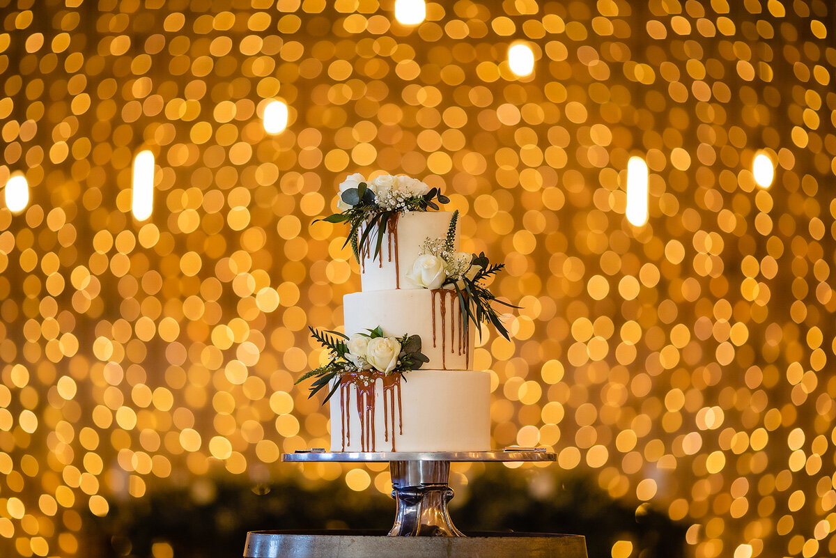 An elegant Naked Wedding Cake with chocolate and flowers at a wedding in the Garden Route.