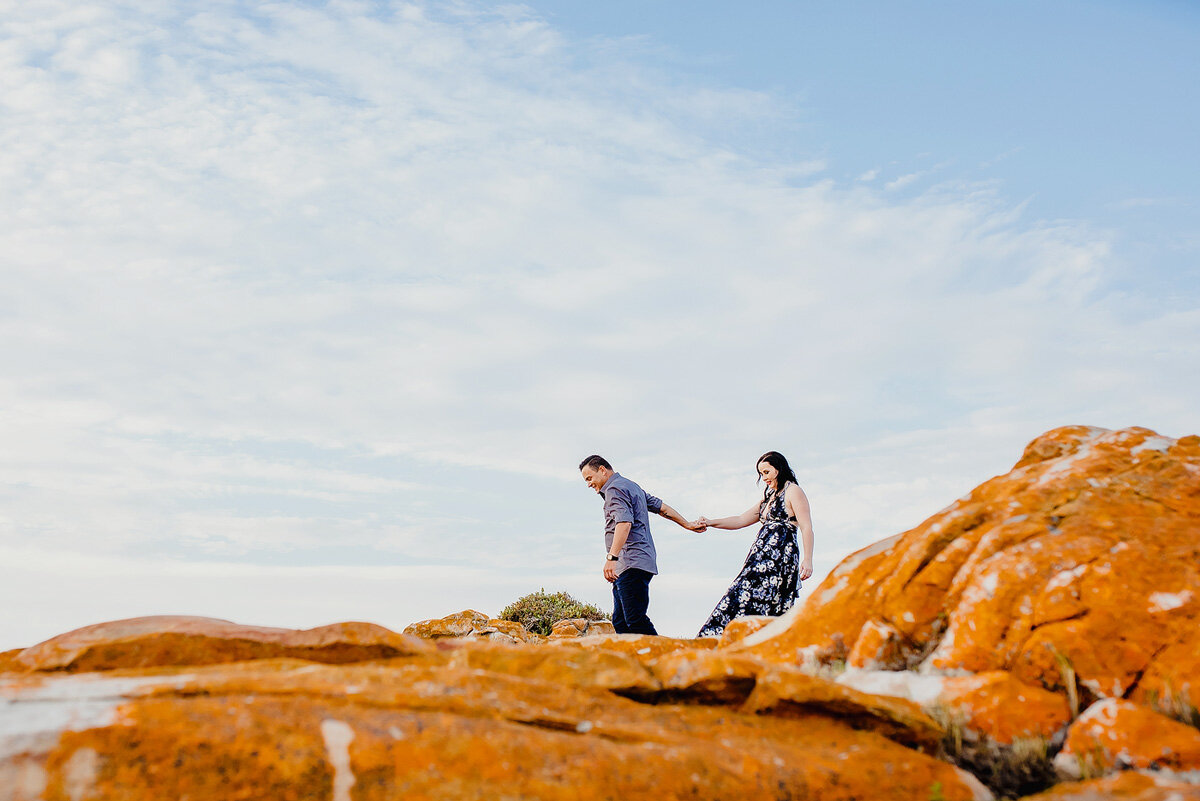Couple walking on orange rocks on shoot